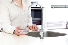 Agua dulce de colada del filtro de ozono en el vidrio de la mujer adentro Imagen de archivo