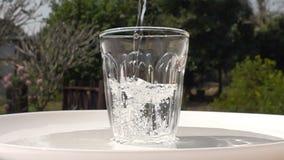 Agua dulce de colada a un vidrio limpio en una placa blanca en fondo natural almacen de metraje de vídeo