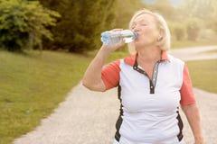 Agua embotellada de consumición de la mujer mayor sana fotografía de archivo