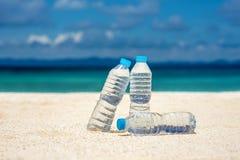 Agua embotellada en un día caliente en la playa Foto de archivo