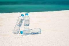 Agua embotellada en un día caliente en la playa Imagen de archivo