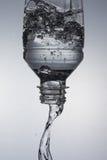 Agua en la botella que cae abajo imagen de archivo