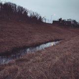 Agua en la zanja por el carril de entrada Imagenes de archivo