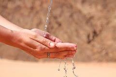 Agua en las manos de la mujer Foto de archivo libre de regalías