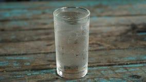 Agua en un vidrio en la tabla fotografía de archivo