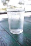 Agua en vidrio en la tabla Imágenes de archivo libres de regalías