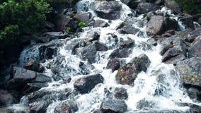 Agua espumosa de precipitación de la cascada rocosa almacen de video