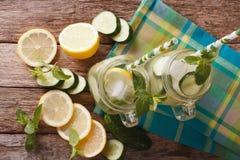 Agua fría con el primer del pepino, del limón, del hielo y de la menta en un vidrio Foto de archivo