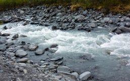 Agua fría que acomete sobre rocas en el desierto de Alaska Imágenes de archivo libres de regalías