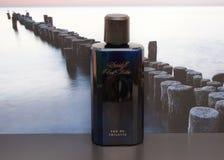 Agua fresca de Davidoff, Eau de Toilette, botella de perfume grande delante de la imagen de un rompeolas en el mar imagen de archivo libre de regalías