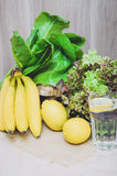 Agua fresca del limón con los limones, los plátanos y la ensalada amarillos de las plantas verdes Dieta, concepto sano, aún vida  Imagenes de archivo