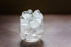agua helada del llano de la forma del corazón de la Aún-vida en vidrio en la tabla con los di Foto de archivo