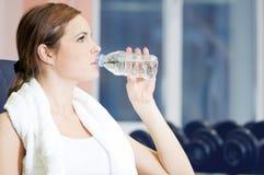 Agua hermosa de la bebida de la mujer del deporte en la gimnasia Imagenes de archivo