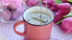 Agua hirvienda caliente vertida sobre la bolsita de té en taza de cerámica rosada, tulipanes rosados y macarrones almacen de video