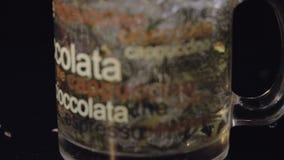 Agua hirvienda de colada en la taza de cristal con las hojas de té verdes secas orgánicas Preparación de té verde Cámara lenta Ti almacen de metraje de vídeo