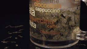 Agua hirvienda de colada en la taza de cristal con las hojas de té verdes secas orgánicas Preparación de té verde Cámara lenta Ti metrajes