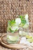 Agua infundida con el pepino, la cal, el hielo y la menta en fondo rústico Bebida del Detox, foco selectivo Foto de archivo