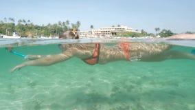 Agua 4k a cámara lenta del océano de las zonas tropicales de la muchacha que bucea almacen de video
