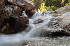 Agua lisa que conecta en cascada sobre rocas imagen de archivo libre de regalías