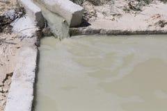 Agua marrón sucia que fluye abajo del canal en la limpieza de la piscina Foto de archivo libre de regalías