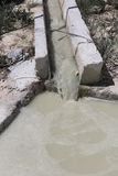 Agua marrón sucia que fluye abajo del canal en la limpieza de la piscina Fotos de archivo libres de regalías