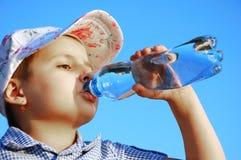 Agua mineral de la bebida del niño Imagenes de archivo