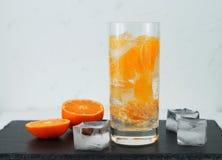 Agua mineral del Detox con la mandarina en fondo blanco y negro foto de archivo