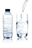 Agua mineral en vidrio y botella Fotos de archivo libres de regalías