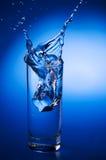 Agua mineral que salpica hacia fuera del vidrio Imagenes de archivo