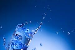 Agua mineral que salpica hacia fuera del vidrio Imagen de archivo libre de regalías