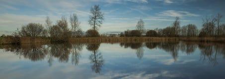 Agua, nubes y árboles Imagen de archivo