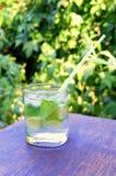 Agua nutritiva del detox con la cal y la menta en un vidrio en el fondo de madera Imagenes de archivo
