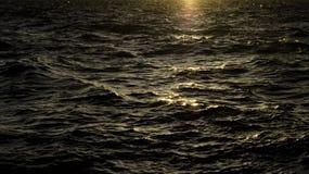 Agua oscura profunda en la puesta del sol con las ondas Foto de archivo libre de regalías