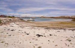 Agua poco profunda en la bahía, playa arenosa, un embarcadero en el fiordo, barco amarrado Foto de archivo libre de regalías