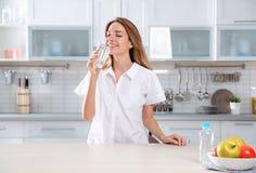 Agua potável bebendo da jovem mulher do vidro imagem de stock