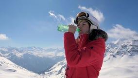 Agua potável bebendo do esquiador da mulher de uma garrafa plástica em um fundo da montanha video estoque