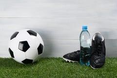 Agua potável em uma garrafa e o conceito do futebol em um gramado verde imagem de stock royalty free
