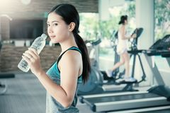 Agua potable asiática de la mujer joven después del ejercicio en club de deporte Imagen de archivo libre de regalías