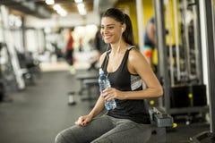Agua potable atractiva de la mujer joven del deporte mientras que se sienta y re fotografía de archivo