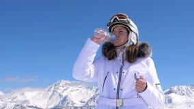 Agua potable de consumición del esquiador de la mujer de una botella plástica en un fondo de la montaña almacen de metraje de vídeo