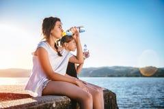 Agua potable de dos muchachas y el sentarse en muelle Foto de archivo