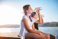 Agua potable de dos muchachas y el sentarse en muelle Foto de archivo libre de regalías