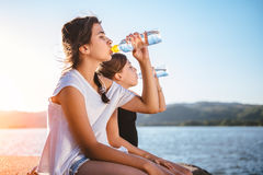 Agua potable de dos muchachas y el sentarse por el mar Foto de archivo libre de regalías