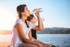 Agua potable de dos muchachas y el sentarse por el mar Imágenes de archivo libres de regalías