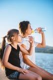 Agua potable de dos muchachas y el sentarse por el mar Fotografía de archivo