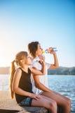 Agua potable de dos muchachas y el sentarse por el mar Fotos de archivo