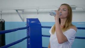 Agua potable de la deportista cansada de la botella después de un entrenamiento duro en el ring de boxeo almacen de video