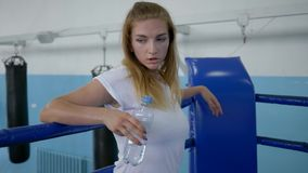 Agua potable de la deportista sedienta de una botella después de un entrenamiento duro en el ring de boxeo almacen de video