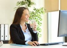 Agua potable de la empresaria en la oficina imagen de archivo libre de regalías