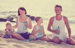 Agua potable de la familia en la playa Foto de archivo